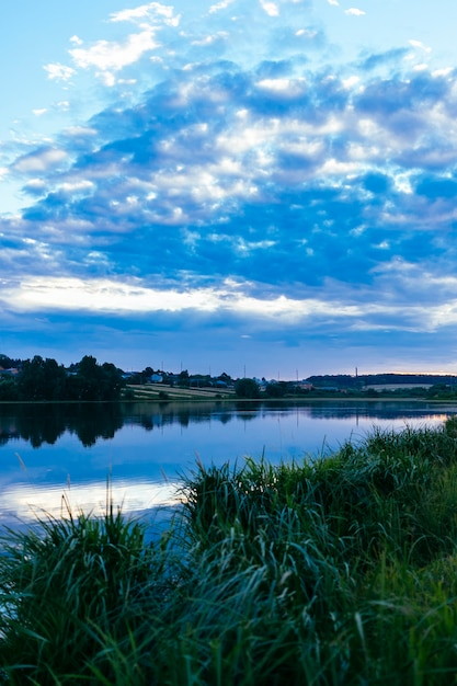 Green grass over the idyllic lake with blue dramatic sky Free Photo