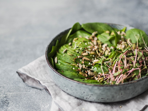 Green healthy salad of spinach, sprouts, avocados and various seeds Premium Photo
