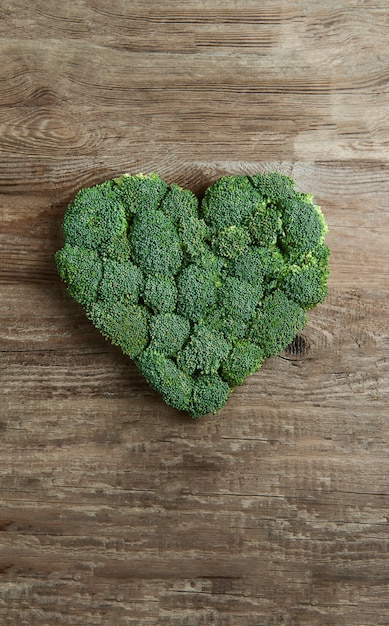 Green heart lined with broccoli on a wooden Premium Photo