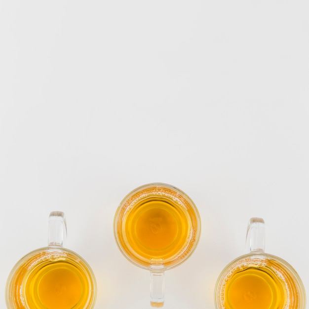 Green herbal glass tea cups on white background Free Photo