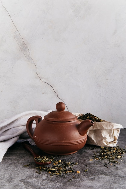 Green herbal teapot with dried tea leaves with napkin against wall Free Photo