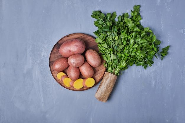 Зеленые травы с картофелем на синем Бесплатные Фотографии