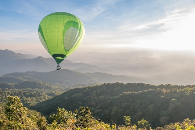 Green hot air balloon over high mountain landscape at sunset Premium Photo