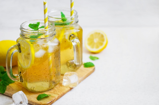 Green ice tea with lemon and mint in a glass jar. Premium Photo