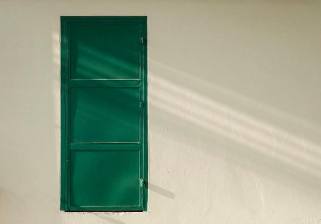 콘크리트 벽 및 복사 공간 녹색 철 문. 프리미엄 사진