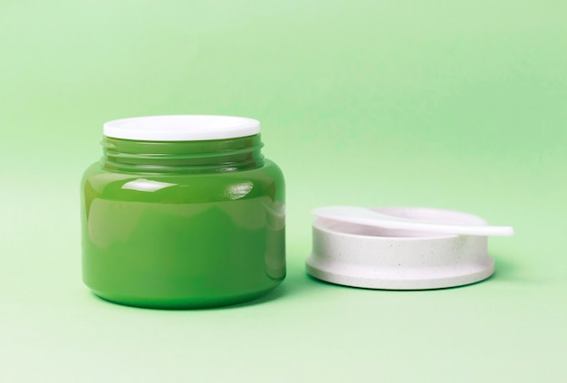 Green jar with white cream and plastic spatula on background, side view, copy space Premium Photo