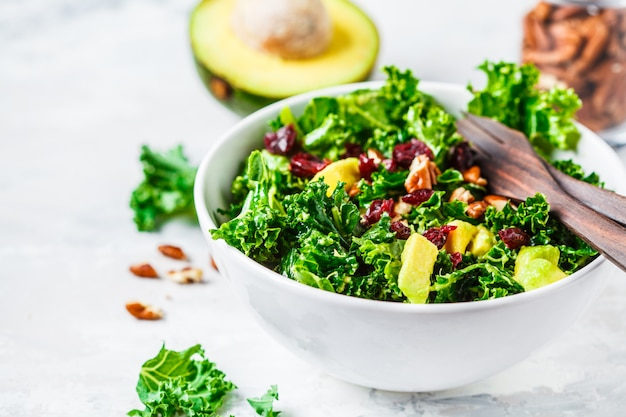 Green kale salad with cranberries and avocado in white bowl. healthy vegan food concept. Premium Photo