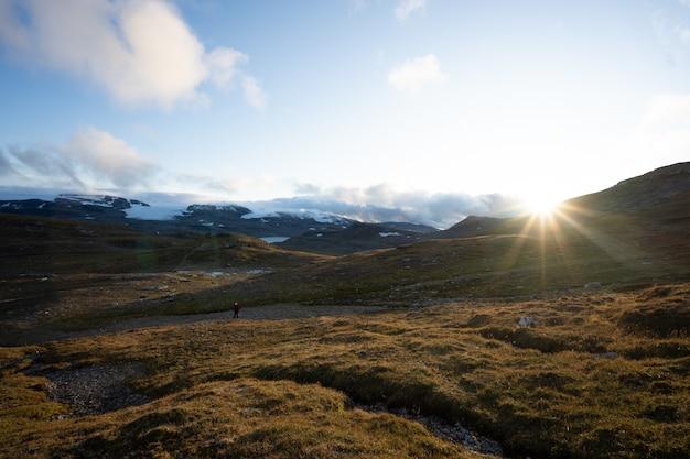 Terra verde circondata da alte montagne rocciose con il sole sullo sfondo a finse, norvegia Foto Gratuite