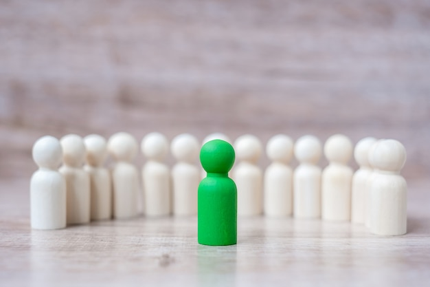 Green leader businessman with crowd of wooden men. leadership, business, team, teamwork and human resource management Premium Photo