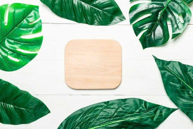 Green leaves around blank wooden board Free Photo