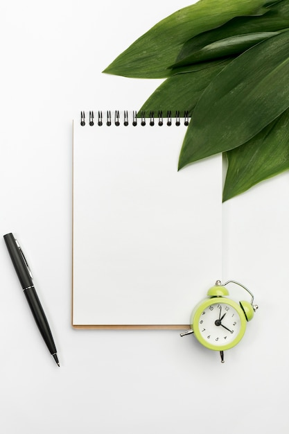 Green leaves on spiral notepad with alarm clock and pen on white backdrop Free Photo