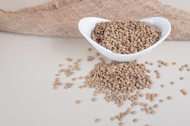 セラミックボウルの緑レンズ豆。 無料写真