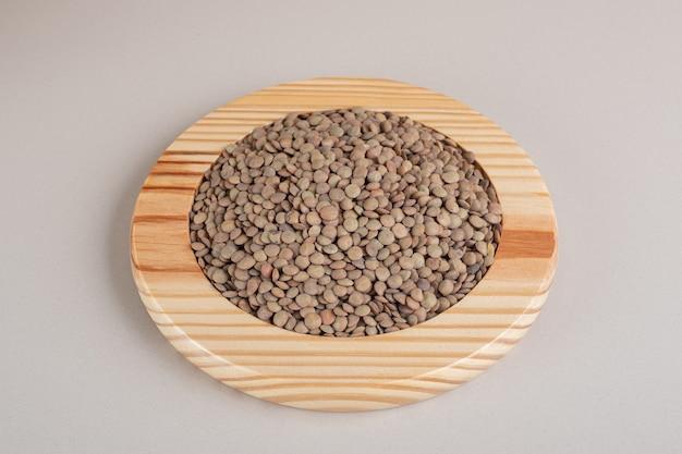 木製の大皿に緑レンズ豆。 無料写真