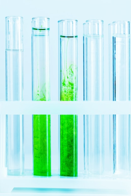 Green liquids in test tubes in chemical laboratory close up Premium Photo