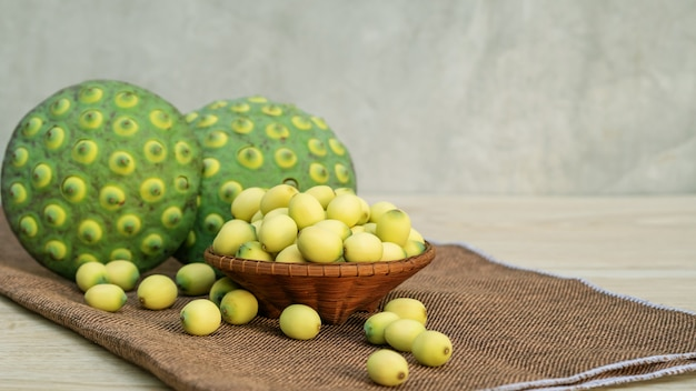Green lotus seeds on a wooden table. Premium Photo