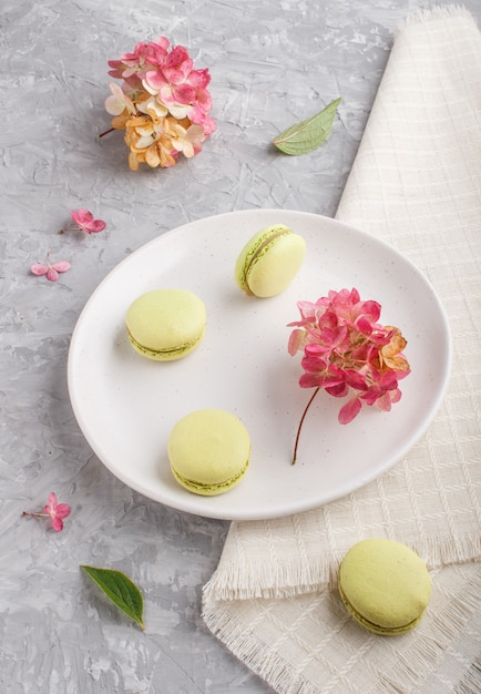 Green macarons or macaroons cakes on white ceramic plate on a gray concrete, side view. Premium Photo