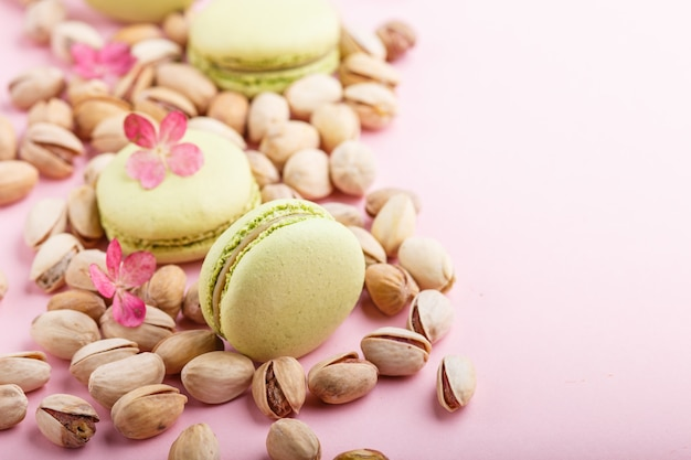 Green macarons or macaroons cakes with pistache nuts. side view, copy space. Premium Photo