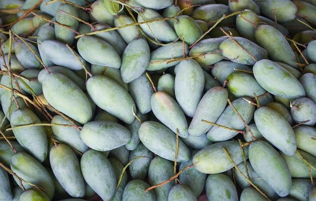 Зеленое манго для продажи на рынке плодоовощ в таиланде. свежий сырой манго текстуру фона урожай из дерева сельского хозяйства азии Premium Фотографии