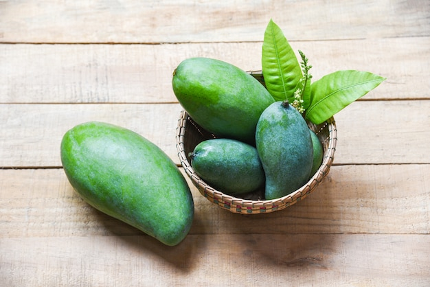 Green mango summer fruit and green leaves in the basket on wood Premium Photo