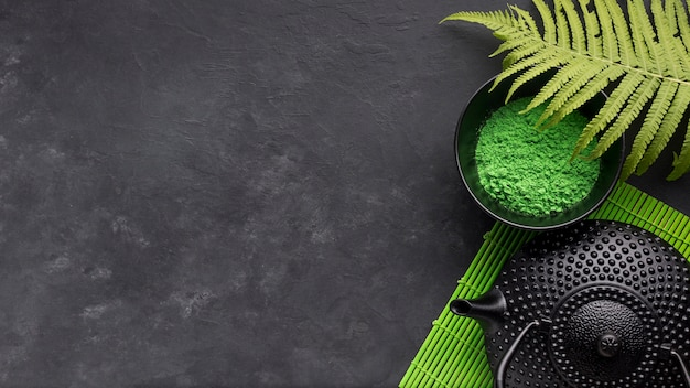 Green match tea powder and fern leaves with black teapot on black background Free Photo