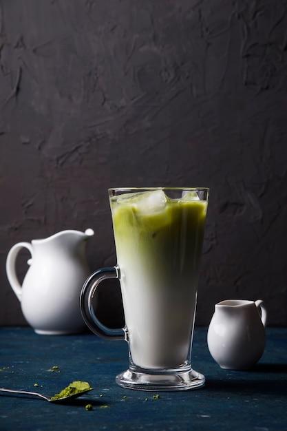 Green matcha powder milk and ice tea summer drink Premium Photo