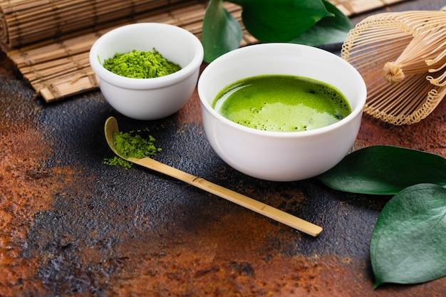 Зеленый чай с напитком и чайные аксессуары на темном ржавом фоне Premium Фотографии
