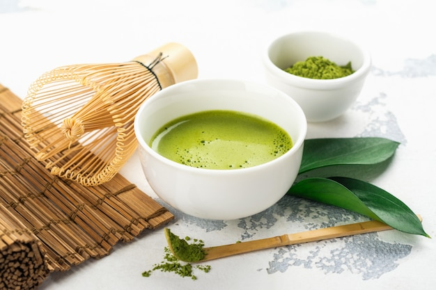 Green matcha tea drink and tea accessories on white background Premium Photo