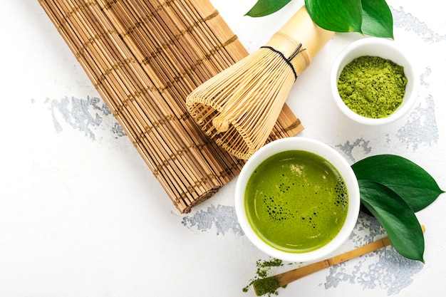 Green matcha tea drink and tea accessories on white background Premium Photo