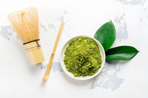 Порошок зеленого чая маття и чайные принадлежности на белом фоне Premium Фотографии