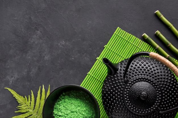 Green matcha tea powder and black teapot on placemat Free Photo
