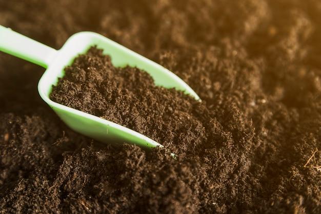 Green measuring scoop in the dark soil Free Photo
