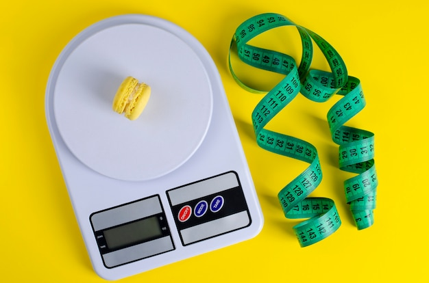 Green measuring tape, digital kitchen scales with macarons on yellow Premium Photo