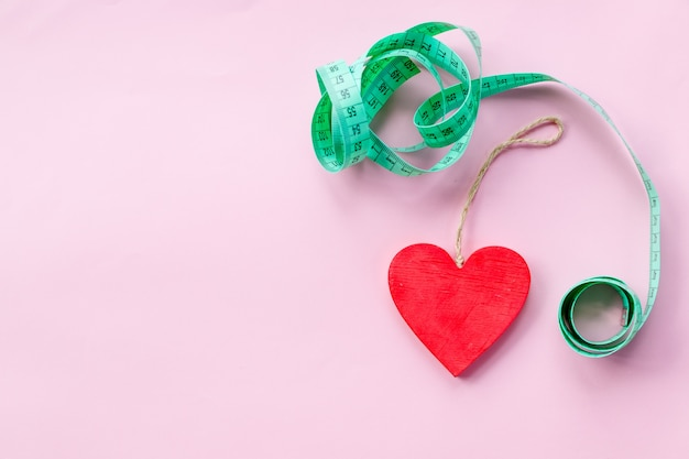Green measuring tape to symbolize an healthy diet Premium Photo