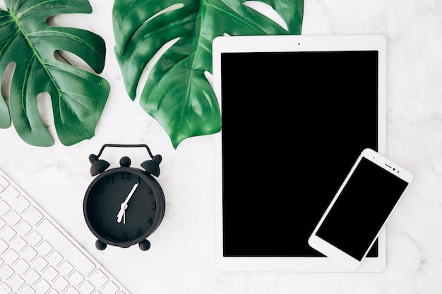 Green monstera leaves; alarm clock; keyboard; digital tablet and mobile phone on textured background Free Photo