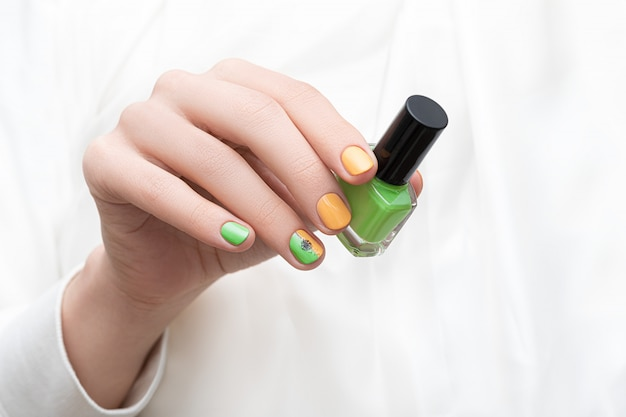 Design delle unghie verde. mano femminile con nail art tarassaco. Foto Gratuite