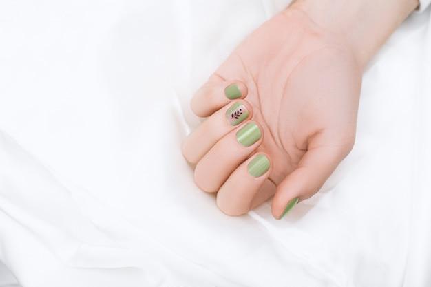 Зеленый дизайн ногтей с черным деревом искусства на средний палец. ухоженная женская рука Бесплатные Фотографии