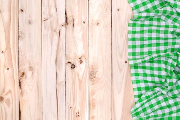 Зеленая салфетка на деревянном столе, вид сверху Premium Фотографии