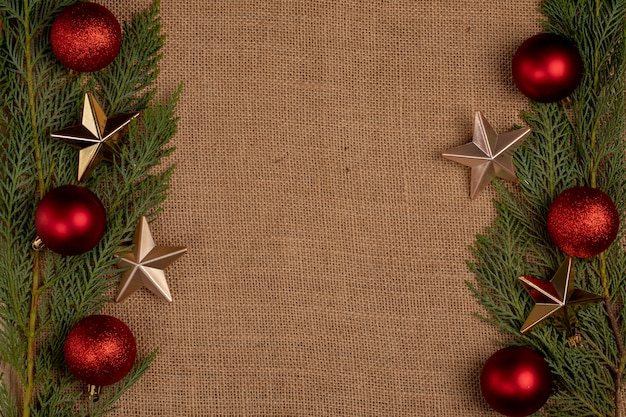 Зеленые ветви дуба с красные елочные шары и золотые звезды с двух сторон. Бесплатные Фотографии