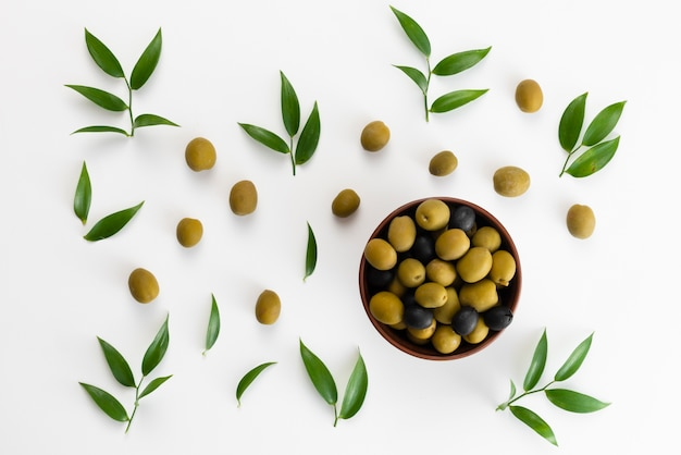 Green olives and black pepper in a bowl top view Premium Photo
