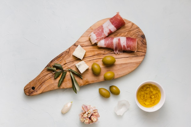 Green olives; cheese; garlic and bacon on wooden chopping board Free Photo