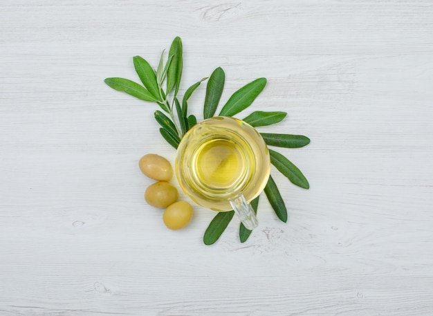 Green olives and olive oil in a glass jar with olive tree branch top view on white wood plank Free Photo