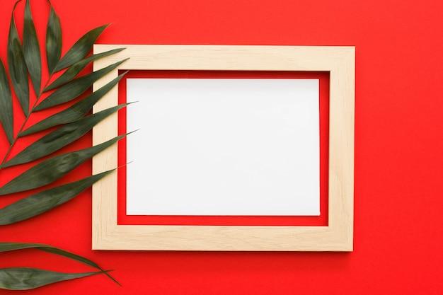 緑のヤシの葉の赤い背景の上の木枠と枝 無料写真