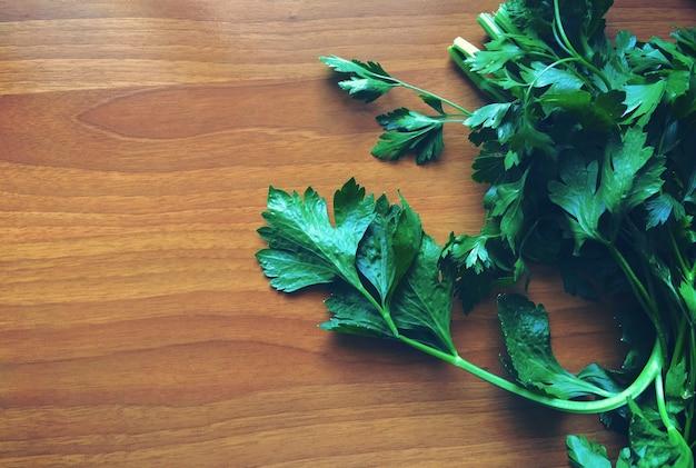 木製のテーブルの左側にある緑のパセリ 無料写真