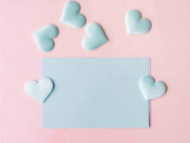 Green pastel card hearts on pink textured Premium Photo