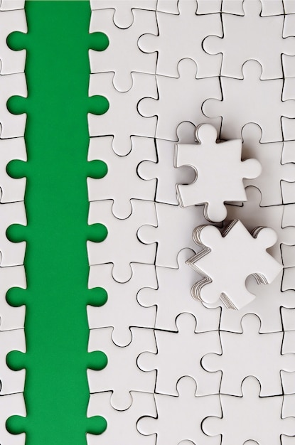 The green path is laid on the platform of a white folded jigsaw puzzle. Premium Photo