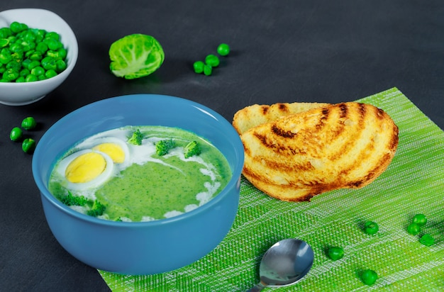 Green pea and broccoli soup with croutons on wooden background Premium Photo