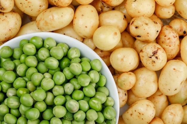 Piselli in una ciotola bianca sulla parete delle patate, primo piano. Foto Gratuite
