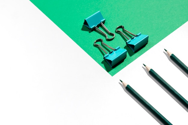 Green pencils and metal binder clips for paper high view Free Photo