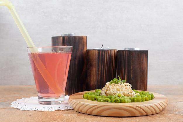 ジュースのガラスと木の板の上の緑のペンネパスタと春雨 無料写真