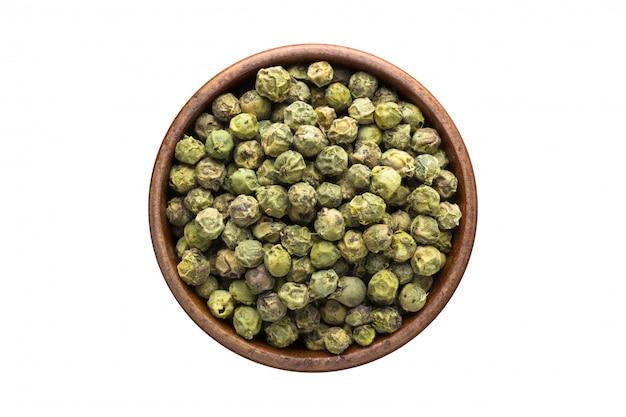 木製のボウルに、白で隔離される緑の胡椒の種子のスパイス。調味料のトップビュー Premium写真